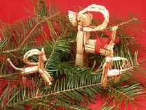 Straw Christmas reindeer. Decorative Christmas reindeer made from straw on pine boughs and a red background Stock Image