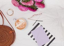Straw circle bag, coffee, flowers and other cute feminine acessories on the white textile background. Top view royalty free stock photography