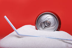 Straw and cola refreshing drink can sitting in pure white sugar mountain Royalty Free Stock Images