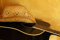 Straw Cowboy Hat on Guitar. Straw cowboy hat resting on black guitar royalty free stock photos