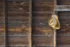 Straw cowboy hat and weathered wood. Straw cowboy hat on the old barn wall  - weathered wood background Royalty Free Stock Photography