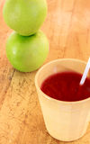 Straw in cup of juice and blur apple ,wood background. Royalty Free Stock Photos