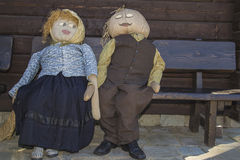 Straw dolls. Two accoutered straw dolls on a bench Stock Photography