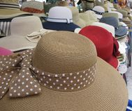 A straw Fashion hat with studs on the ribbon. Colonial style straw sun hats with ribbons in different colors on a market in Verona in Italy Stock Photo