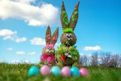 Straw Figure Bunny With Colorful Easter Eggs green grassand blue sky Easter And Spring Background. royalty free stock photography