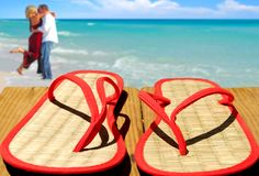 Straw Flip Flops and couple. Flip flops on pier with couple in distance royalty free stock image