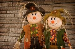 Straw Folks. A pair of straw people standing side by side in front of an old stone wall Stock Image