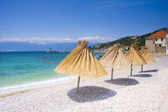 Straw gamps. Lined up on the shingly beach in Baska, Croatia Royalty Free Stock Photography