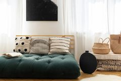 Straw handbags next to stylish black vase and fancy sofa with pillows made of futon, black poster on the wall between windows. Straw handbags next to stylish royalty free stock photo