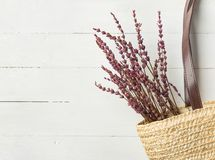 Straw handwoven beach shoulder bag with leather handles lavender flowers bouquet on white plank wood background. Provence style. Straw handwoven beach shoulder royalty free stock image