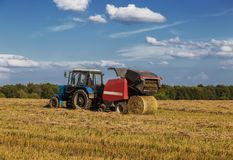 Straw harvesting with the help of a rotary roll forming machine in the unit with a tractor. Sunny day royalty free stock photography