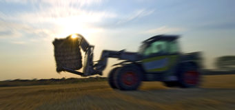 Straw harvesting with tractor Stock Images