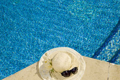The straw hat. Lies on the brink of pool stock photo