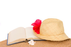 Straw hat ans book on sand Stock Images