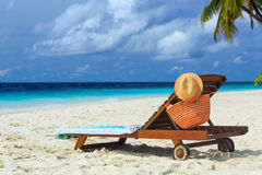 Straw hat and bag on a lounge chair at tropical beach Royalty Free Stock Image