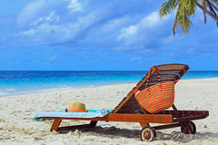 Straw hat and bag on a lounge chair at tropical beach Stock Photos