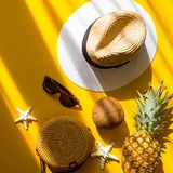 Straw hat, bamboo bag, sunglasses, coconut, pineapple, starfish over yellow background, top view. Colorful summer female fashion outfit flat lay. Straw hat royalty free stock images