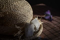 Straw hat on the bamboo tablecloth Stock Photos