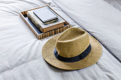 Straw hat on bed. With tray of books Royalty Free Stock Image
