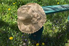 Straw hat on a bench. Hat on a bench in the shade. Rest after hard work royalty free stock photography