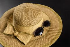 Bow Straw Hat and Sunglasses. Straw hat with a big bow on a dark wooden background, with a pair of sunglasses royalty free stock photo