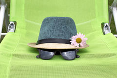 Straw hat with black glasses on a green chair royalty free stock photos