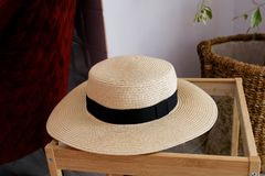 A straw hat with a black ribbon is on the coffee table in the living room. Plants in the background. Close up royalty free stock photos