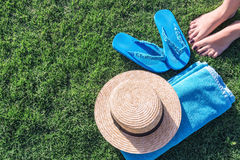 Straw hat, blue towel and flip flops royalty free stock image