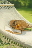 Straw hat and book on lace hammock Stock Photography