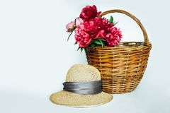 Straw hat with a bouquet of luxurious pink peonies stock photos