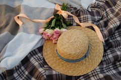 Straw hat and a bouquet of pink roses on a plaid royalty free stock photos