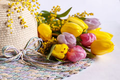 Straw hat with bouquets of tulips. Straw hat with a bouquet of yellow and pink tulips on white background Royalty Free Stock Images