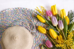 Straw hat with bouquets of tulips. Straw hat with a bouquet of yellow and pink tulips on white background Stock Photos