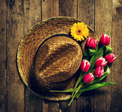 Straw hat with bunch of purple tulip flowers on vintage wooden t Stock Images