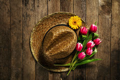 Straw hat with bunch of purple tulip flowers on vintage wooden t Royalty Free Stock Photo