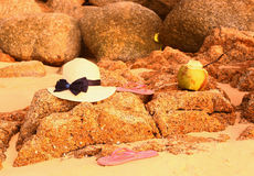 Straw hat coconut  flip flops on the stony beach Royalty Free Stock Image