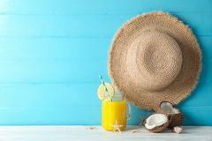 Straw hat, coconuts, fresh orange juice and starfishes on white table against color wooden background, space for text. Summer vacation backdrop stock photos