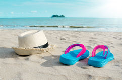 Straw hat and colorful flip flops on beach against sunny sky. Summer vacation concept Royalty Free Stock Images