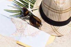 Straw Hat com um cartão do turista na areia Fotos de Stock Royalty Free