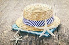 Straw Hat con el libro y las estrellas de mar en la tabla de madera Imagen de archivo