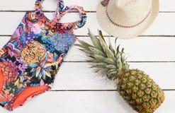 Straw Hat, costume da bagno tropicale della stampa, ananas Vecchio fondo di legno bianco fotografie stock