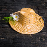 Straw hat with daisies flower on black cracks background, close Stock Photography