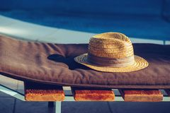 Straw hat on deck chair by the swimming pool. In summer morning royalty free stock image