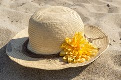 Straw hat decorated with flower placed on the sandy beach Royalty Free Stock Images