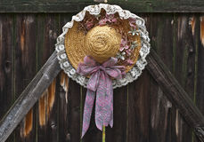 Straw Hat Decoration. Spring motif straw hat hanging on an old, weathered wooden gate Royalty Free Stock Photo