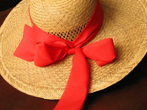 Straw hat (detail). Straw hat with red bow on dark background royalty free stock photo