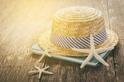 Straw Hat en la tabla de madera con el libro y las estrellas de mar Imágenes de archivo libres de regalías