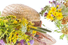 Straw hat and field flowers. Retro beauty of a rural life Stock Photos