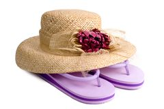Straw Hat and Flip Flops. Ladies straw hat with flower decoration and purple flip-flops stock photography