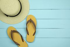 Straw hat and flip flops on light green wooden background. royalty free stock photography